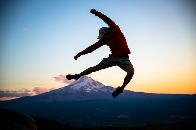 man jumping in air in front of mountain at sunset