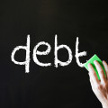 """the word """"debt"""" on a chalkboard along with a hand holding an eraser"""