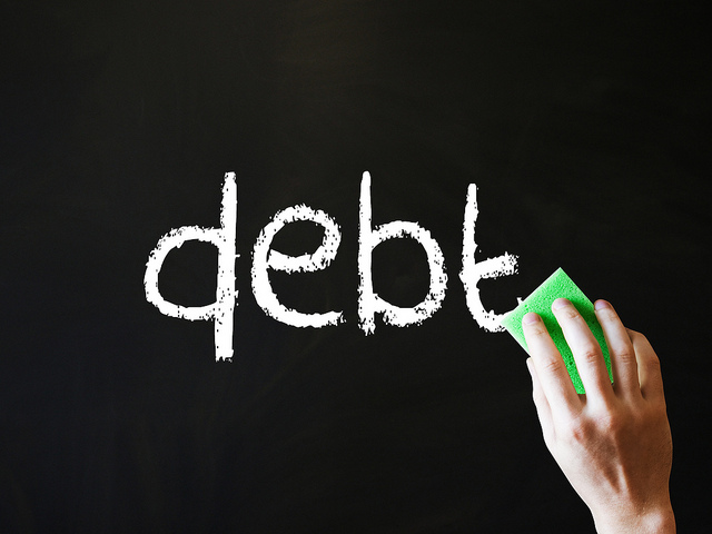 "the word ""debt"" on a chalkboard along with a hand holding an eraser"